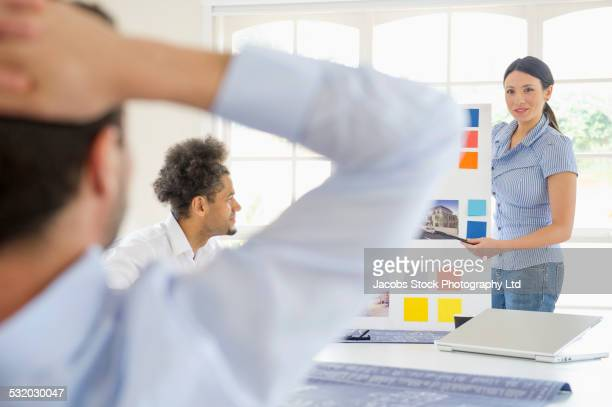 Businesswoman presenting to colleagues in conference room