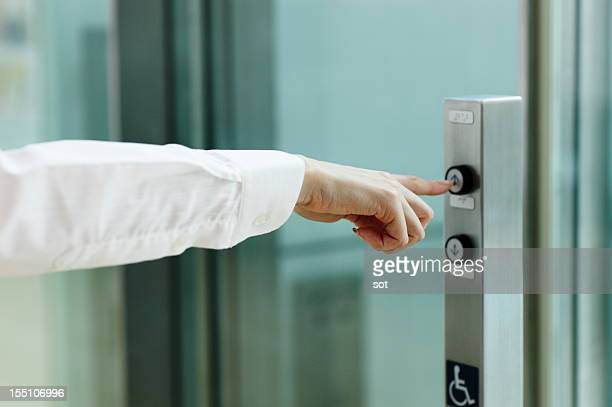 Businesswoman pressing button for elevator