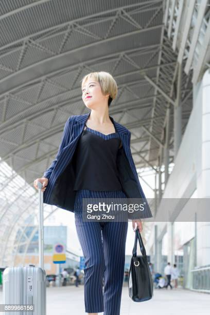 businesswoman pulling a suitcase walking in railway station