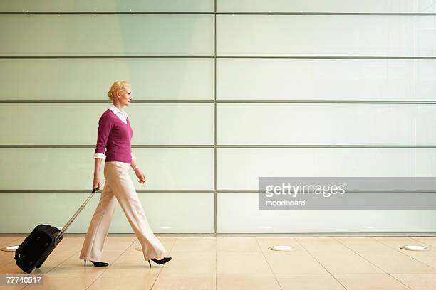 Businesswoman Pulling Carry On Suitcase