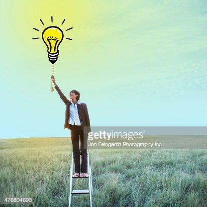 Businesswoman pulling chain on light bulb illustration