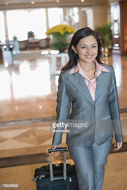 Businesswoman pulling her luggage and smiling