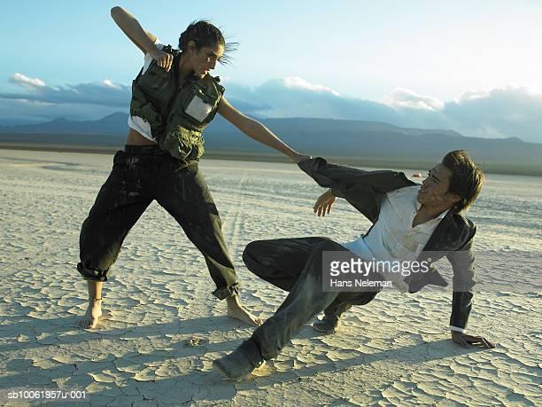 Businesswoman punching businessman in desert