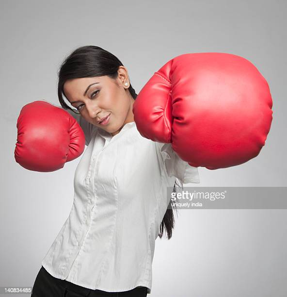 Businesswoman punching with boxing gloves