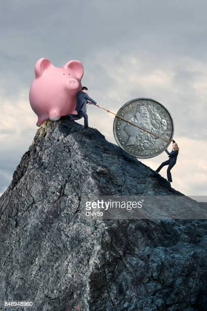 Businesswoman Pushing And Businessman Pulling Silver Dollar Up Steep Mountain