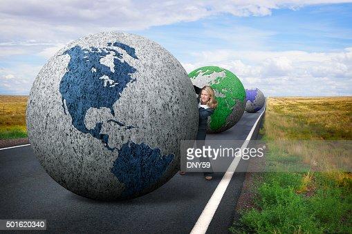 Businesswoman Pushing Globe Down Rural Road