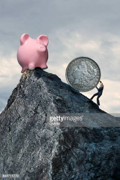 Businesswoman Pushing Silver Dollar Up Steep Mountain
