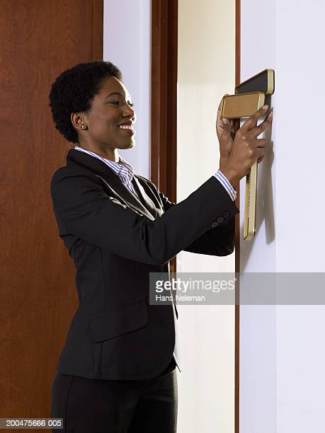 Businesswoman putting nameplate on wall in office, smiling, side view