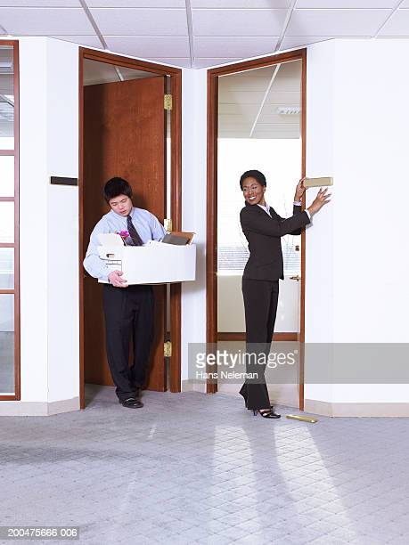 Businesswoman putting nameplate on wall, man carrying away box