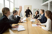 Businesswoman raising hand up at diverse team meeting sitting at conference table, student asking senior teacher mentor coach questions during seminar lecture training, corporate education concept