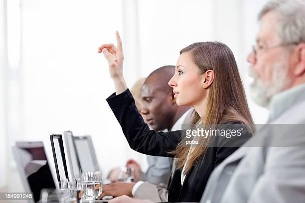 Geschäftsfrau Anhebung hand bei business-meeting