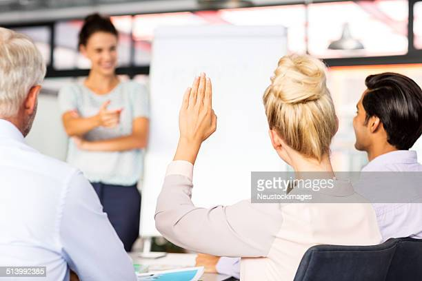 Businesswoman Raising Hand To Answer During Seminar