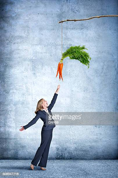 Businesswoman Reaching For A Dangling Carrot On A Stick