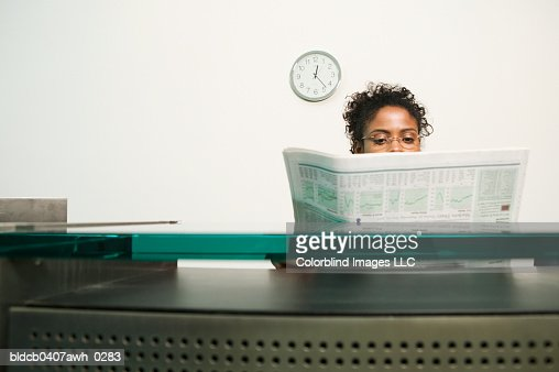 Businesswoman reading a newspaper : Stock Photo