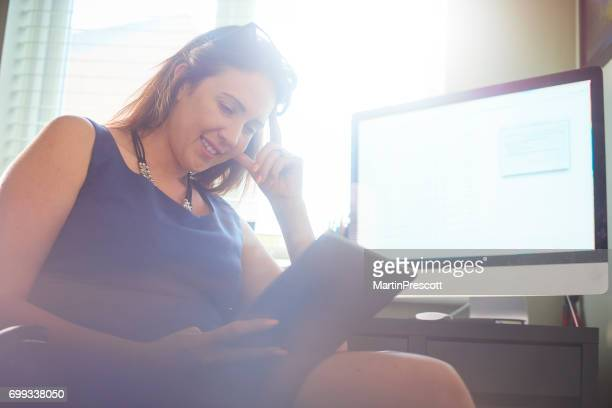 Businesswoman reading document on digital tablet