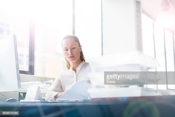 Geschäftsfrau Lesen von Dokumenten am Schreibtisch in Büro