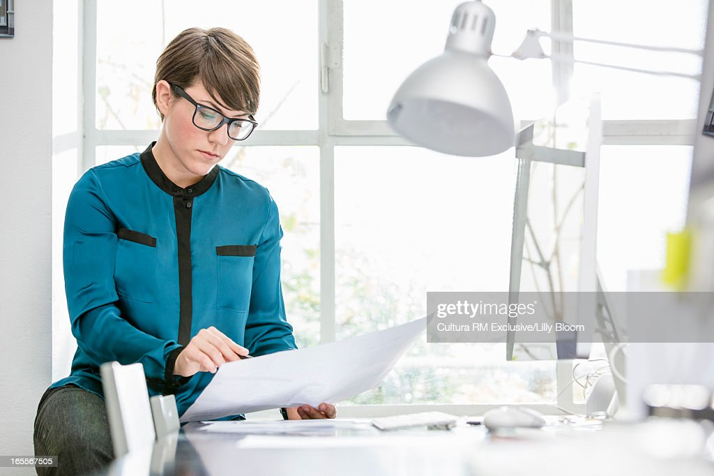 Businesswoman reading in office : Stock Photo