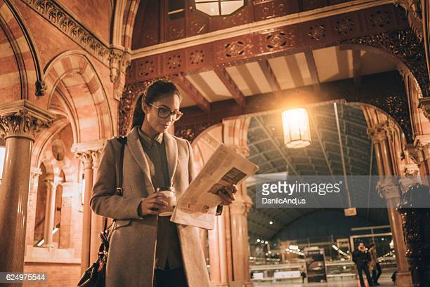 businesswoman reading newspaper after work