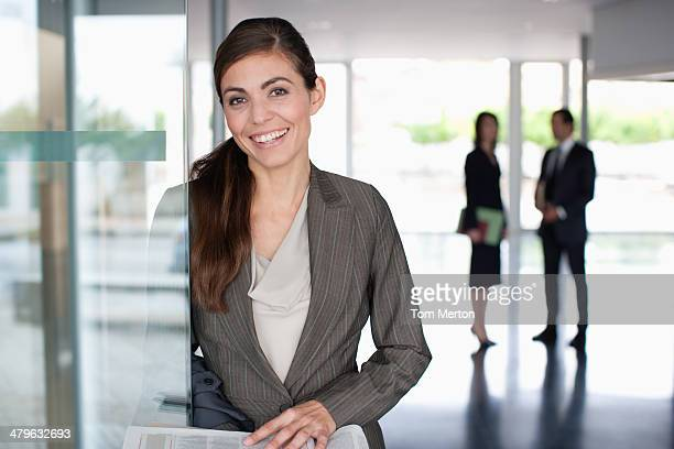 Businesswoman reading newspaper in office lobby