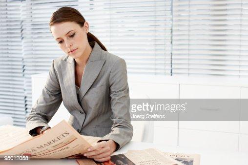 Businesswoman reading newspaper : Stockfoto