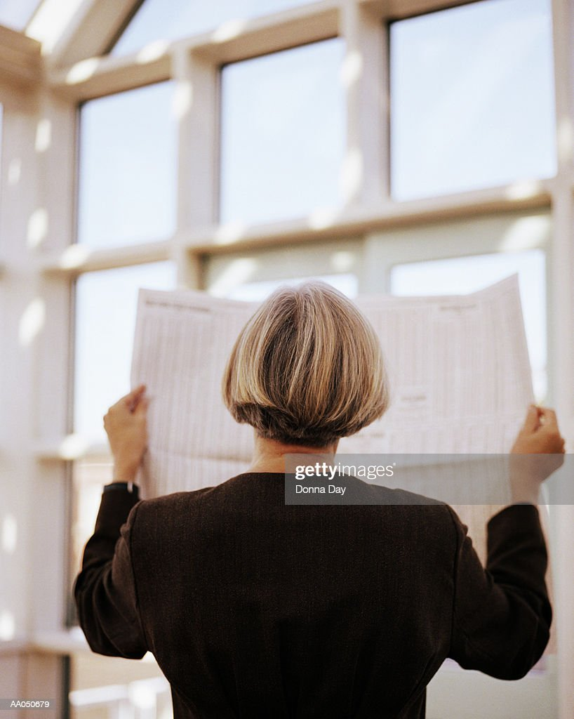 Businesswoman reading newspaper, rear view : Stock Photo