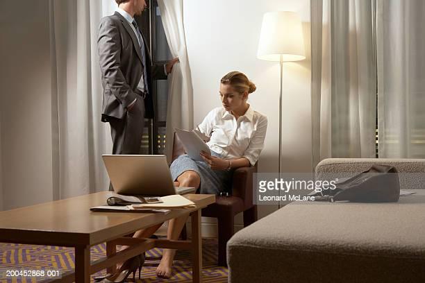 Donna d'affari di leggere i documenti cartacei, Uomo d'affari in piedi dalla finestra