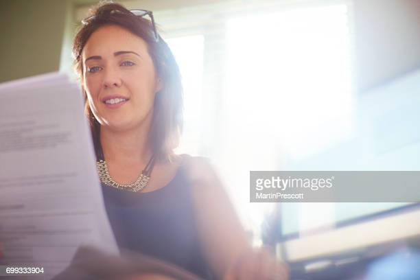 Businesswoman reading through documents at her desk