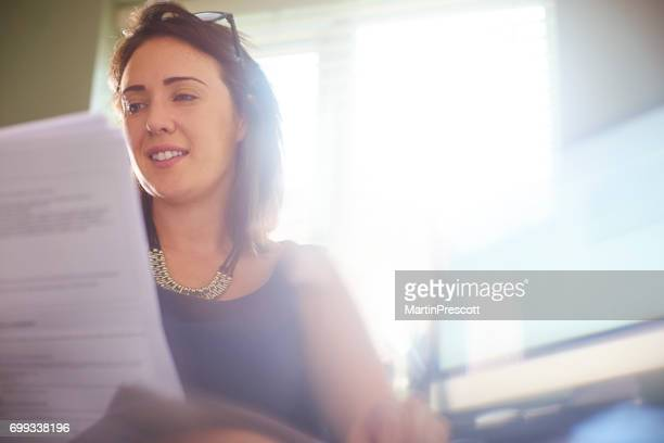 Businesswoman reading through documents in her office