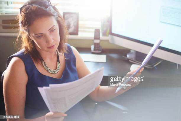 Businesswoman reads through client paperwork