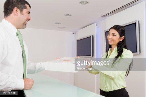 Businesswoman receiving a parcel from a businessman : Foto de stock