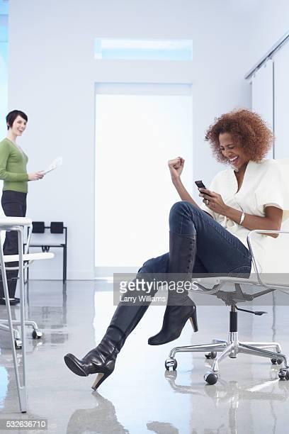 Businesswoman Receiving Good News Via Text Message