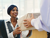 Businesswoman receiving package from delivery man in office
