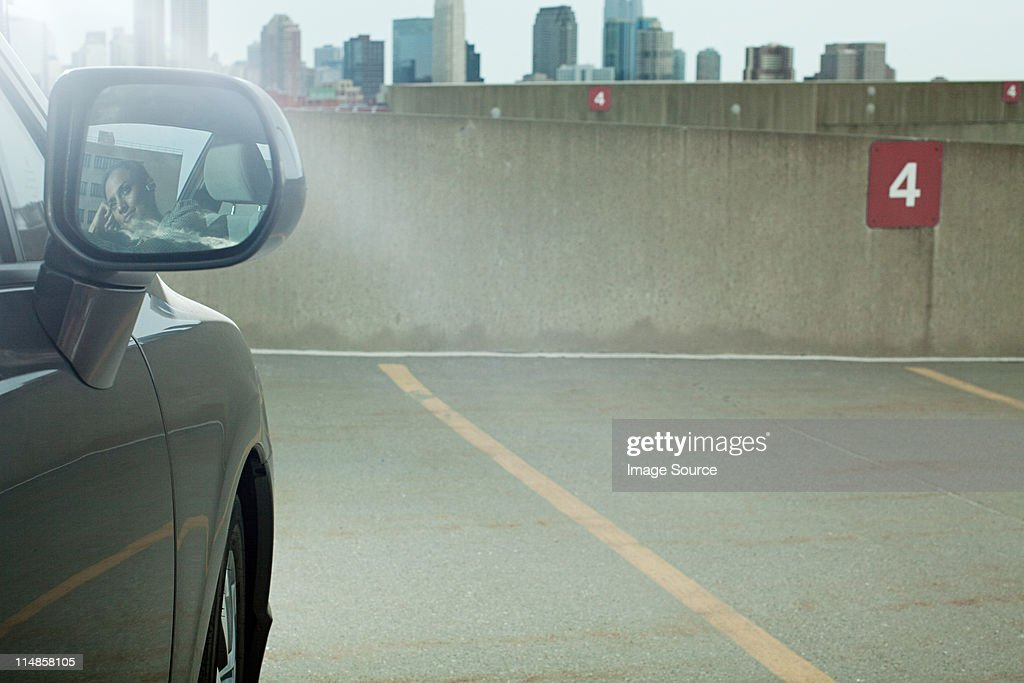 Businesswoman reflected in wing mirror of car in car park : Stock Photo