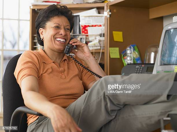 Businesswoman relaxing and talking on the phone at her desk