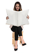 businesswoman sitting on wooden chair on white background with legs crossed reads the newspaper, on white background