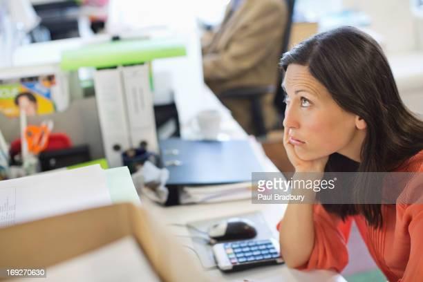 Businesswoman resting chin in hand on desk