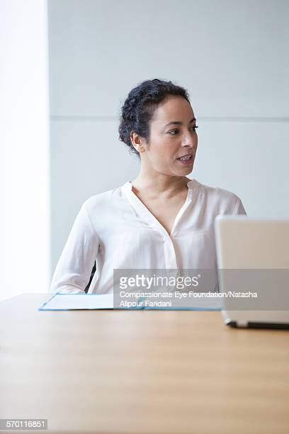 Businesswoman reviewing paperwork in board room