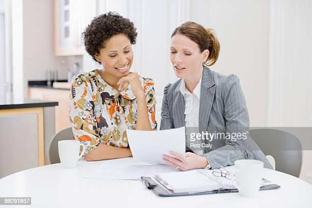 Femme d'affaires examinant des documents avec femme
