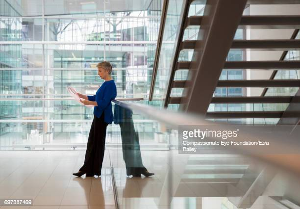 Businesswoman reviewing project in office hallway