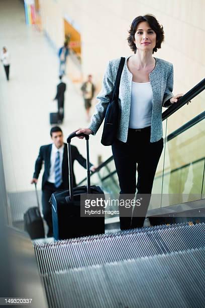 Businesswoman riding escalator