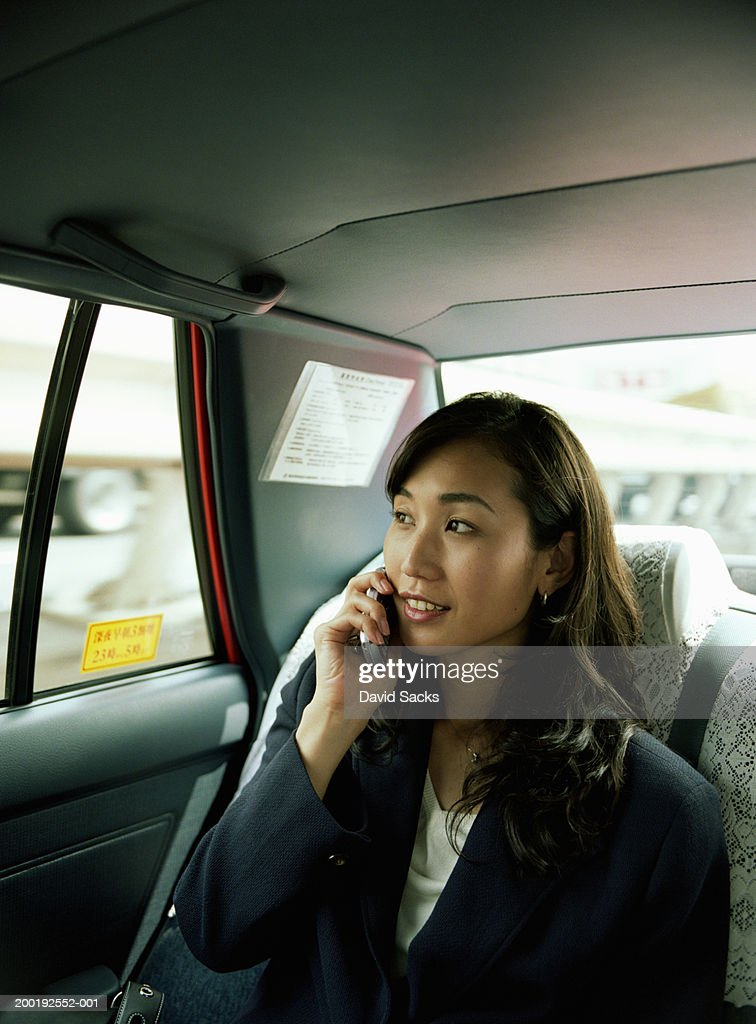Businesswoman riding in car, using mobile phone : Stock Photo