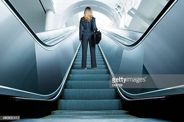 Femme d'affaires remonter un escalier roulant