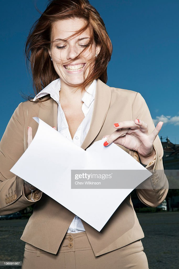 Businesswoman ripping paper outdoors : Stock Photo