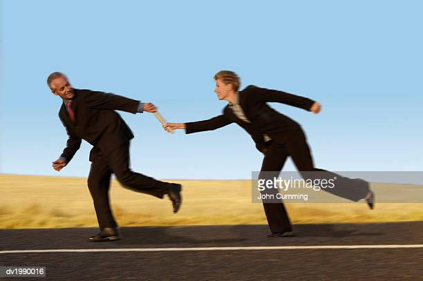 Businesswoman Running and Passing a Relay Baton to a Businessman on a Country Road