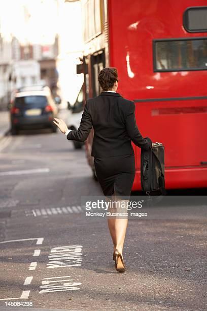 Businesswoman running for bus