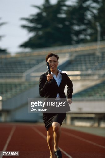 Businesswoman running relay race : Stock Photo