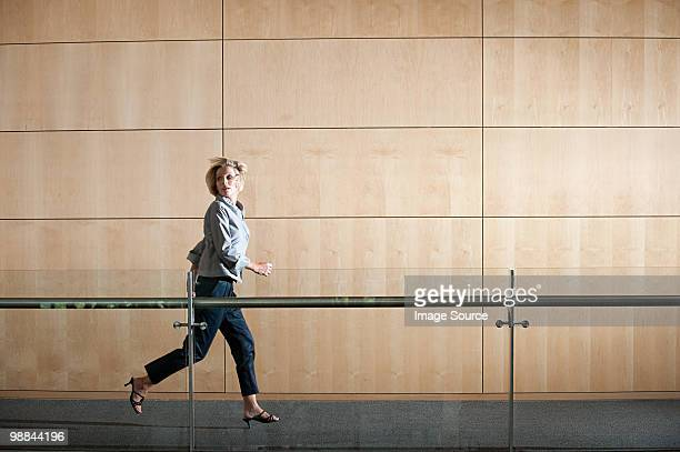 Businesswoman running through corridor