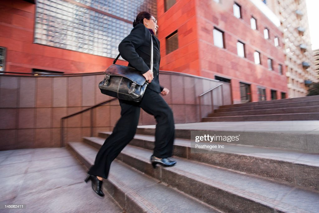 Businesswoman running up steps