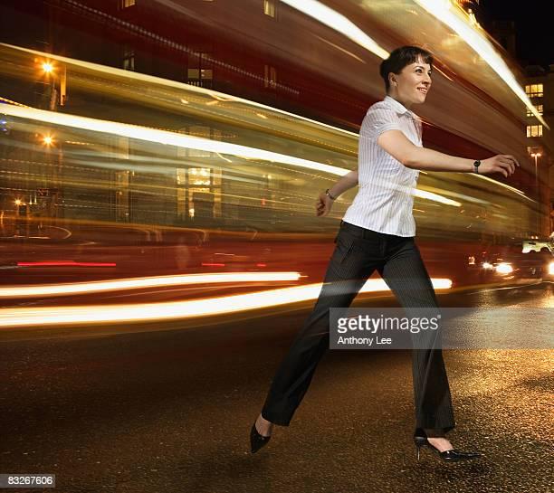 Businesswoman running with lights streaking behind