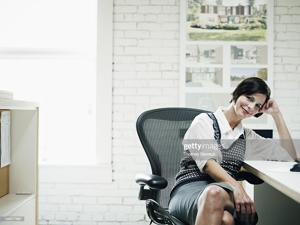 Businesswoman seated at desk in office smiling : Stock Photo